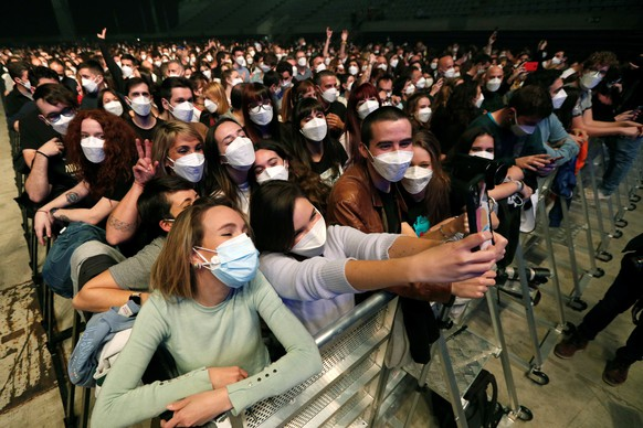 epa09101745 Members of the audience take a selfie as the Spanish band Love of Lesbian performs on stage in front of 5,000 people at the Palau Sant Jordi arena in Barcelona, Catalonia, Spain, 27 March 2021. This is the first crowded concert in Spain since the beginning of the COVID-19 coronavirus pandemic a year ago. People had to go through a PCR test and were given FPP2 masks before entering the test concert venue.  EPA/Alejandro Garcia