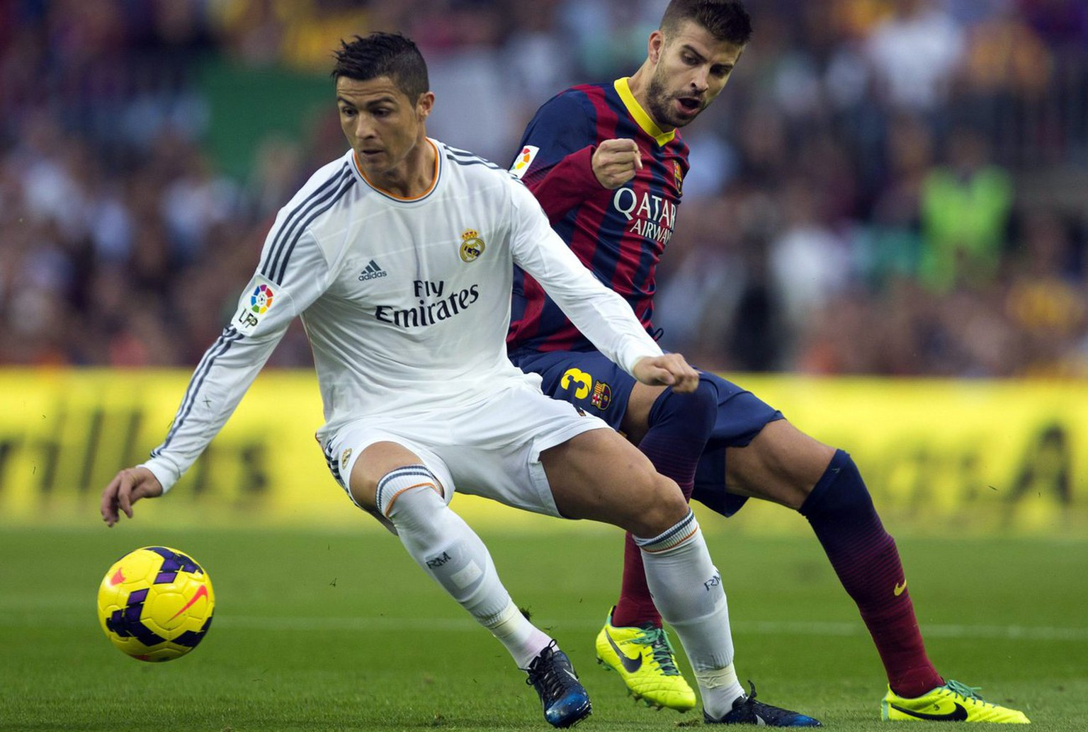 epa03925664 Real Madrid's Cristiano Ronaldo (L) in action agaisnt FC Barcelona's Gerard Pique (R) during the Spanish Primera Division league soccer match between Barcelona and Real madrid at Camp Nou stadium in Barcelona, Spain, 26 October 2013.  EPA/Alejandro Garcia