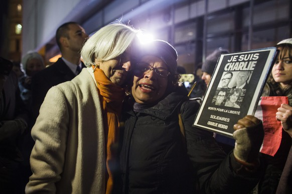 epa04550279 International Monetary Fund (IMF) Director Christine Lagarde (L) greets a participant in a vigil for the victims of the attack on the Paris offices of satirical magazine Charlie Hebdo outside the Newseum in Washington, DC, USA, 07 January 2015. Earlier in the day, masked gunmen with automatic rifles killed 12 people at the Paris headquarters of satirical French magazine Charlie Hebdo, which had angered Muslims two years ago by publishing cartoons of Muhammad.  EPA/JIM LO SCALZO