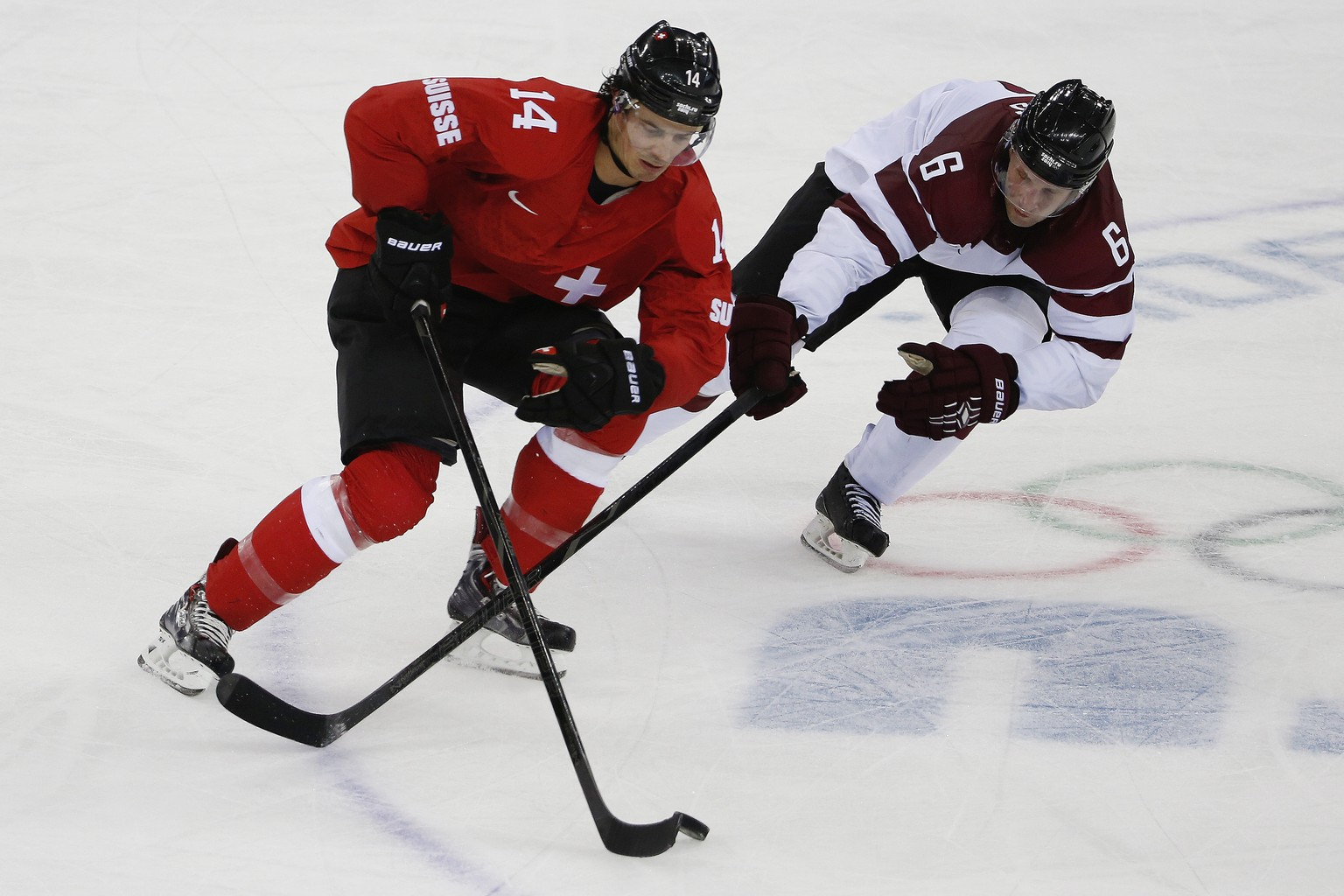 Latvia defenseman Arvids Rekis tries to take control of the puck from Switzerland forward Roman Wick during the second period of the 2014 Winter Olympics men's ice hockey game at Shayba Arena, Wednesday, Feb. 12, 2014, in Sochi, Russia. (AP Photo/Petr David Josek)