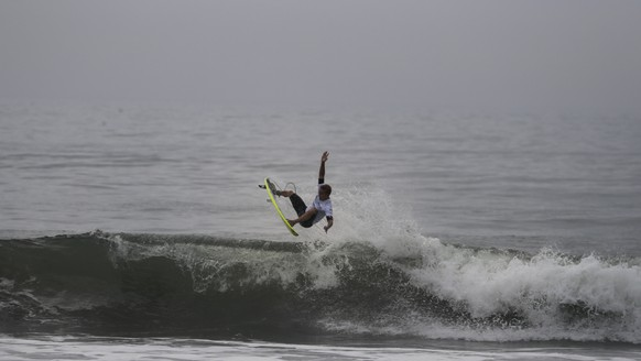 In this Thursday, July 18, 2019, photo, a surfer competes during a test event at Tsurigasaki beach, a venue for surfing at the Tokyo 2020 Olympics, in Ichinomiya, Chiba prefecture, east of Tokyo. One the most popular surfing spots in Japan, Tsurigasaki was chosen because it has more consistent waves than other locations near Tokyo. (AP Photo/Jae C. Hong)