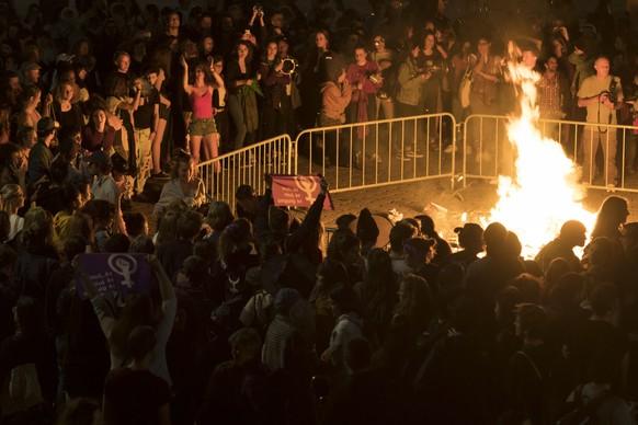 Des femmes brulent une pancarte dans un feu sur la place de la Riponne lors d'une action de lancement de la greve des femmes / greve feministe ce vendredi 14 juin 2019 a Lausanne. (KEYSTONE/Laurent Gillieron)