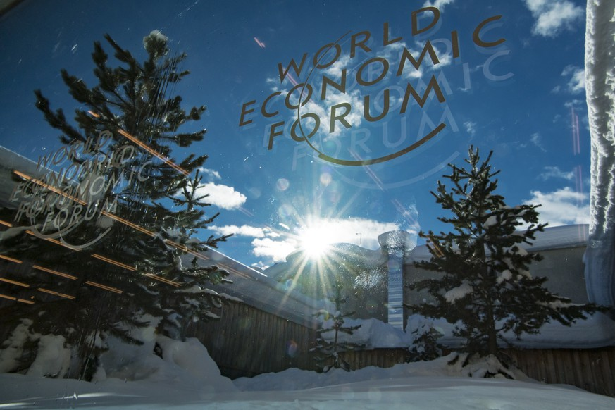 A WEF logo is pictured on a window of the Congress Center in front of snow covered trees two days prior to the 49th Annual Meeting of the World Economic Forum, WEF, in Davos, Switzerland, Sunday, January 20, 2019. The meeting brings together entrepreneurs, scientists, corporate and political leaders in Davos under the topic