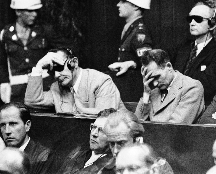 Hermann Goering, left, and Rudolf Hess listen to the verdict of the War Crimes Tribunal at Nuernberg, Germany on Sept. 30, 1946. At right rear is Admiral Karl Doentiz (with dark glasses). (AP Photo)
