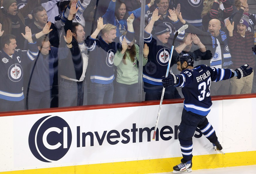 Winnipeg Jets' Dustin Byfuglien (33) celebrates his overtime goal against the Minnesota Wild in an NHL hockey game Tuesday, Feb. 10, 2015, in Winnipeg, Manitoba. The Jets won 2-1. (AP Photo/The Canadian Press, Trevor Hagan)