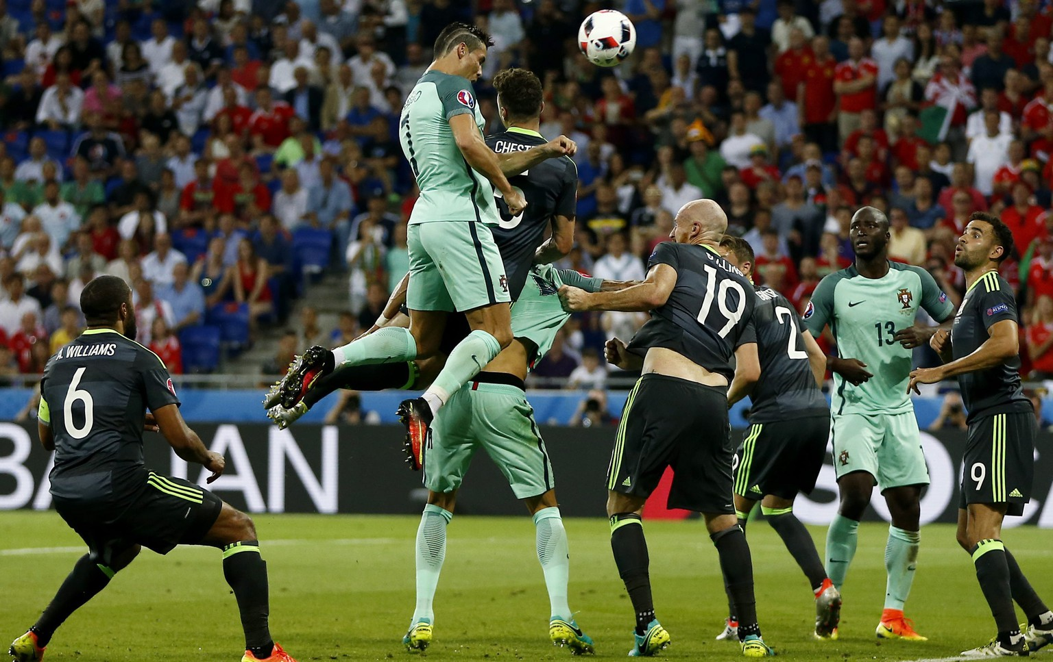 epa05411749 Cristiano Ronaldo (C-L) of Portugal goes for a header to score the opening goal during the UEFA EURO 2016 semi final match between Portugal and Wales at Stade de Lyon in Lyon, France, 06 July 2016.