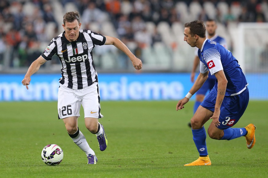 Juventus' defender Stephen Lichtsteiner fights for the ball with Cesena's defender Antonio Mazzotta during the Italian Serie A football match Juventus Vs Cesena on September 24, 2014 at Juventus  Stadium in Turin.  AFP PHOTO / MARCO BERTORELLO