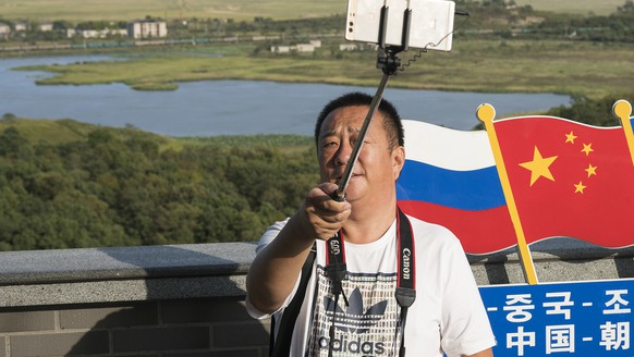 In this Saturday, Sept. 9, 2017 photo, a man takes selfie at the border which separates China, North Korea and Russia, in Yanbian in China's Jilin province. The United States has called for a vote Monday on a U.N. resolution that would impose the toughest-ever sanctions on North Korea and could lead to a showdown with the country's biggest trading partner China and its neighbor Russia. (AP Photo)