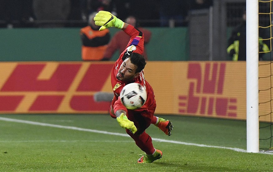 Dortmund goalkeeper Roman Buerki catches a penalty during the German Soccer Cup match between Borussia Dortmund and Hertha BSC Berlin in Dortmund, Germany, Wednesday, Feb. 8, 2017. (AP Photo/Martin Meissner)