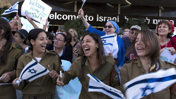 epa04350032 Israeli soldiers among people cheering a group of 338 Americans and Canadians arriving at Ben Gurion Airport, in Lod, outside Tel Aviv, Israel, 12 August 2014. According to media reports, about 100 new arrivals coming from 27 states of the USA and some from Canada, are men and women planning to serve in the Israeli Army.  EPA/JIM HOLLANDER