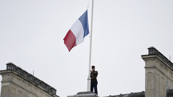 epa05986788 A Republican guard flies the French flag at half mast on the roof of the Elysee Palace in tribute to the victims of the May 22 terror attack in Manchester, Paris, France, 24 May 2017. At least 22 people were killed and around 59 others were injured in the 22 May 2017 attack that occured at the end of a concert by US singer Ariana Grande in Manchester.  EPA/STEPHANE DE SAKUTIN/ POOL MAXPPP OUT