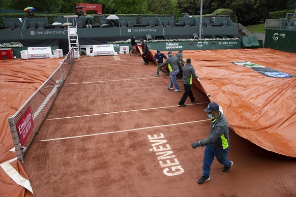 epa09207134 Staff remove the rain cover from the court during the first round match between Benoit Paire of France and Dominik Keeper of Germany at the ATP 250 Geneva Open tennis tournament in Geneva, Switzerland, 17 May 2021.  EPA/SALVATORE DI NOLFI