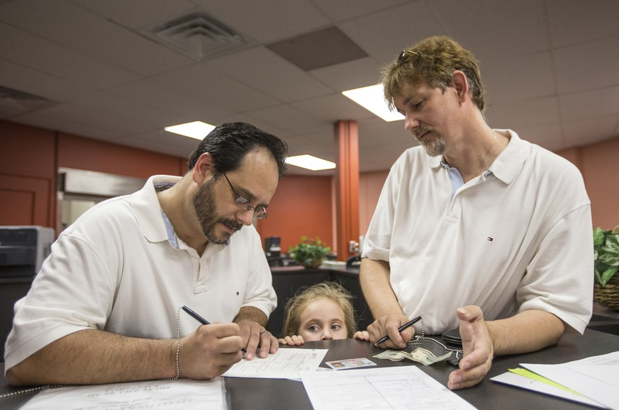 Greg Bovo, left, and his partner David Schmokel fill out a marriage license application as their adopted daughter, Sophia Bovo-Schmokel, 5, looks on inside the County Clerk's office in the St. Joseph County Courthouse on Wednesday, June 25, 2014, in South Bend, Ind. (AP Photo/South Bend Tribune, Robert Franklin)
