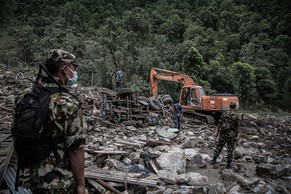 KATHMANDU, NEPAL - AUGUST 04: Rescue teams search near damaged houses at the scene after a landslide, on August 4, 2014, in Sindhupalchowk district, Nepal. Over 20 dead bodies have been found while rescue operation continues two days after a massive landslide in Northern Nepal, More than 100 residents are still missing. (Photo by Lam Yik Fei/Getty Images)