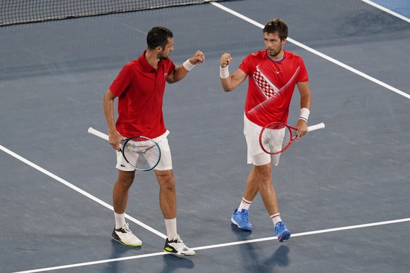 Nikola Mektic, right, and Mate Pavic, of Croatia, bump fists during the quarterfinal round of men's doubles tennis competition against Kei Nishikori, and Ben McLachlan, of Japan, at the 2020 Summer Olympics, Wednesday, July 28, 2021, in Tokyo, Japan. (AP Photo/Patrick Semansky) Nikola Mektic,Mate Pavic