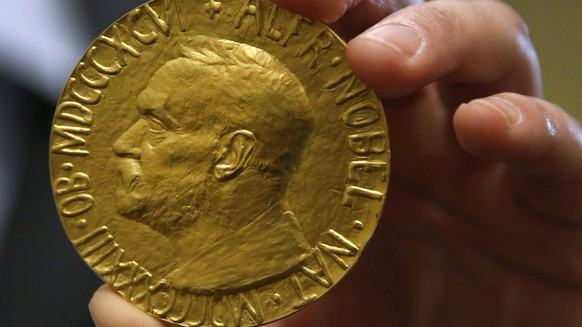 Bidder Ole Bjorn Fausa, of Norway, holds the 1936 Nobel Peace Prize in Baltimore, Thursday, March 27, 2014, the second Nobel Peace Prize ever to come to auction. The prize sold for a winning bid of $950,000 at auction, and an additional buyer's commission brought the final sale price to $1.16 million.  The recipient was Argentina's foreign minister, Carlos Saavedra Lamas, who was honored for his role in negotiating the end of the Chaco War between Paraguay and Bolivia. (AP Photo/Patrick Semansky)