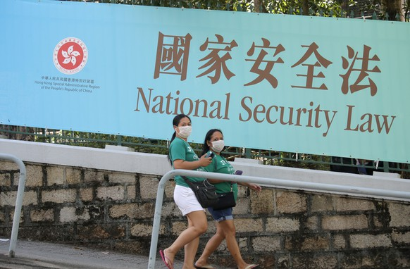 Women walk past a promotional banner of the national security law for Hong Kong, in Hong Kong, Tuesday, June 30, 2020. China has approved a contentious law that would allow authorities to crack down on subversive and secessionist activity in Hong Kong, sparking fears that it would be used to curb opposition voices in the semi-autonomous territory.(AP Photo/Kin Cheung)