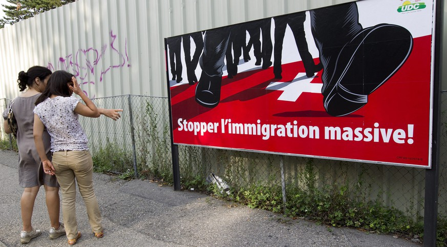 Women look a poster of the rightwing Swiss People's Party (SVP/UDC) which shows feet walking on the Swiss cross and the message