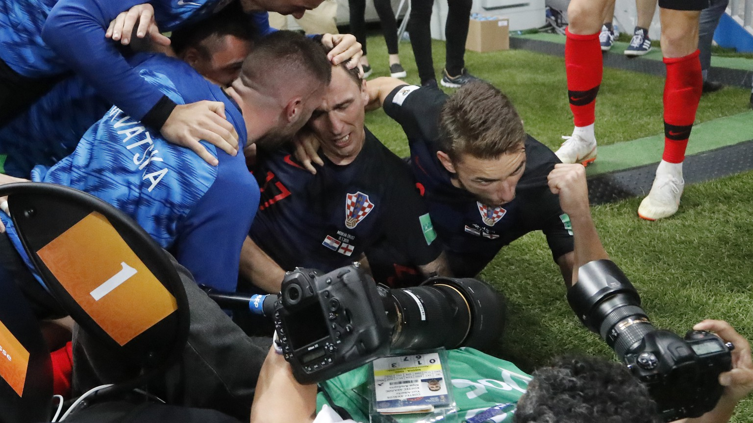 Croatia's Mario Mandzukic sits between his teammates after falling over a photographer when celebrating after scoring his side's second goal during the semifinal match between Croatia and England at the 2018 soccer World Cup in the Luzhniki Stadium in Moscow, Russia, Wednesday, July 11, 2018. (AP Photo/Frank Augstein)