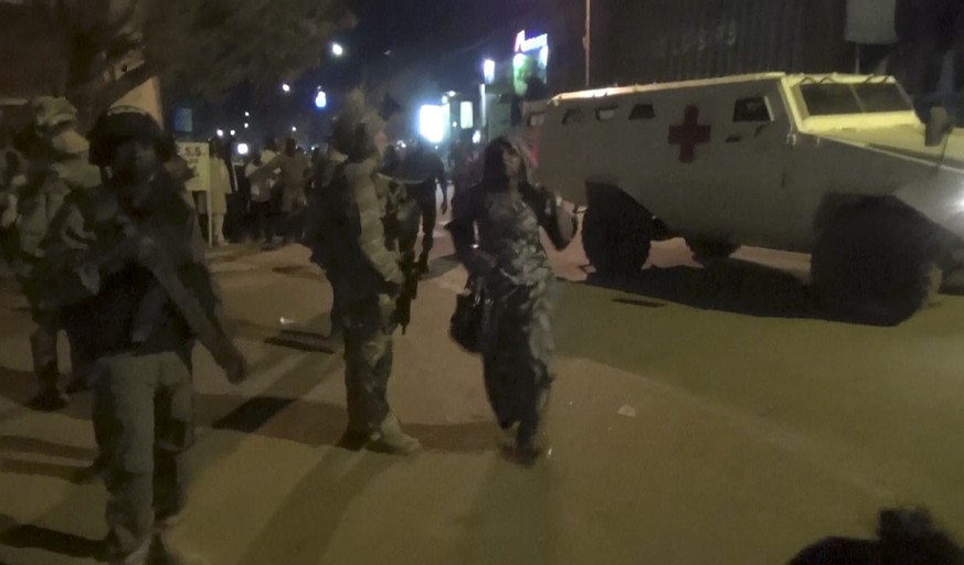 In this image taken from video from AP Television, a freed woman, center, walks past French special forces near the Splendid Hotel, early Saturday, Jan. 16, 2016, in Ouagadougou, Burkina Faso. Heavy gunfire erupted early Saturday as forces from Burkina Faso and France worked to overtake the luxury hotel that had been seized by al-Qaida militants the night before. (AP Television via AP)