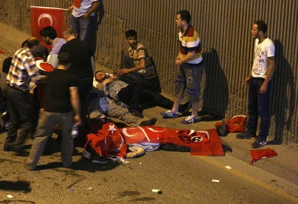 ATTENTION EDITORS - VISUAL COVERAGE OF SCENES OF INJURY OR DEATH - People react as bodies draped in Turkish flags are seen on the ground during an attempted coup in Ankara, Turkey July 16, 2016.  REUTERS/Stringer ATTENTION EDITORS - THIS IMAGE WAS PROVIDED BY A THIRD PARTY. EDITORIAL USE ONLY. NO RESALES. NO ARCHIVES. TURKEY OUT. NO COMMERCIAL OR EDITORIAL SALES IN TURKEY.       TEMPLATE OUT
