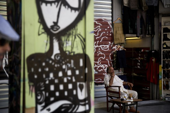 """A shop owner sits a a chair as he waits for customers, in Kos, Greece, Monday, July 6, 2015. Greece's Finance Minister Yanis Varoufakis has resigned following Sunday's referendum in which the majority of voters said """"no"""" to more austerity measures in exchange for another financial bailout.  (AP Photo/Petros Giannakouris)"""