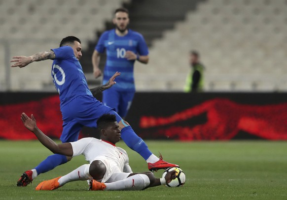 Switzerland's Breel Embolo, front, duels for the ball with Greece's Tasos Donis during an international friendly soccer match between Greece and Switzerland at the Olympic stadium in Athens, Friday, March 23, 2018. (AP Photo/Thanassis Stavrakis)