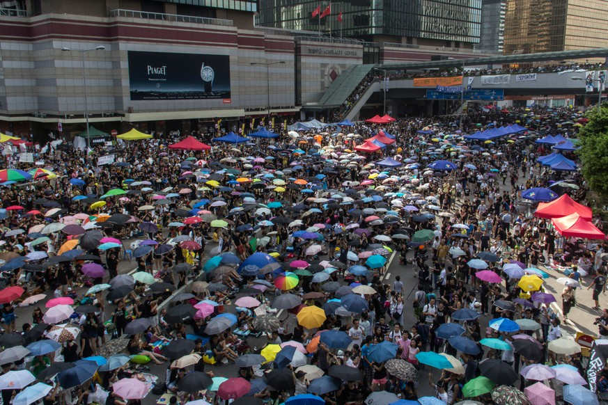 Pro-democracy protesters raise their umbrellas on cue as part of the demonstrations currently blocking central Hong Kong that have been dubbed the