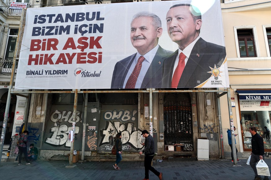 epa07466962 People walk in front of the pictures of Turkish President Recep Tayyip Erdogan (R) and Candidate of Justice and Development Party (AK Party) for Istanbul mayor Binali Yildirim (C), in Istanbul, Turkey, 27 March 2019. Local elections in Turkey's capital and the country's overall 81 provinces are scheduled for 31 March.  EPA/TOLGA BOZOGLU