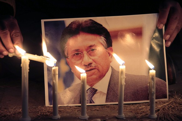 epa04065252 Supporters of former Pakistani president and military ruler Pervez Musharraf light candles in front of a portrait photo of him during a rally in Islamabad, Pakistan, 09 February 2014. A Pakistan court set another deadline for former military ruler Pervez Musharraf to appear after he did not show up on 07 February for a scheduled indictment on treason charges. It was the fourth court appointment Musharraf has missed since the trial began in December. Judge Faisal Arab said the special tribunal would issue a warrant for the former president's arrest if he fails to attend the next hearing on 18 February. Musharraf, who faces treason charges for abrogating the constitution in 2007, is being treated at a military hospital in Pakistan after complaining of chest pains while being driven to court on 02 January.  EPA/SOHAIL SHAHZAD