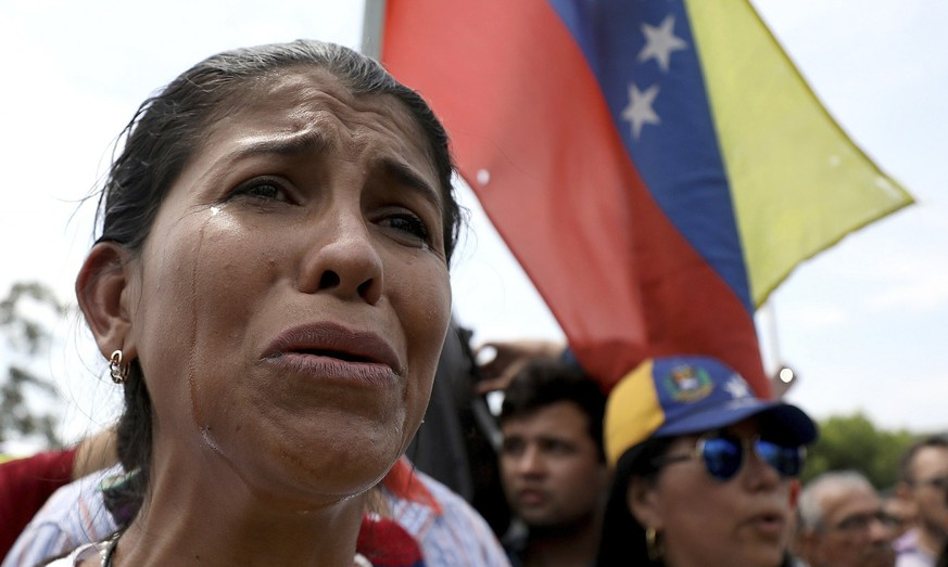 Venezuelan migrant Yanela Aleman cries as she sings her national anthem in La Parada, near Cucuta, Colombia, on the border with Venezuela, Sunday, Feb. 17, 2019. As part of U.S. humanitarian aid to Venezuela, Sen. Marco Rubio, R-Fla is visiting the area where the medical supplies, medicine and food aid is stored before it it expected to be taken across the border on Feb. 23. (AP Photo/Fernando Vergara)