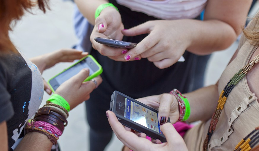 Three women use their smartphones at the