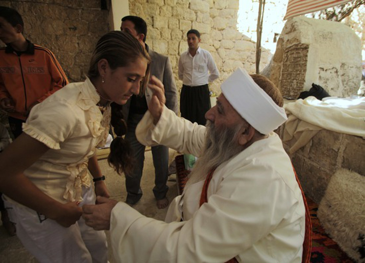 A Yazidi religious leader blesses a worshipper during the community's main festival of Eid al-Jamma, which lasts for a week, at Lalish temple in a small mountain valley situated northwest of Mosul, 390 km (240 miles) north of Baghdad October 7, 2010. Yazidis are members of a pre-Islamic Kurdish sect who live in northern Iraq and Syria. The community was a target for the deadliest militant attacks in Iraq since 2003 when suicide truck bombings killed more than 400 Yazidi people in August 2007. Picture taken October 7, 2010.    REUTERS/Stringer (IRAQ - Tags: RELIGION SOCIETY)