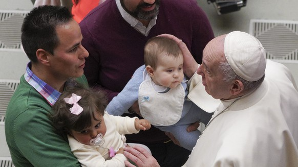 Pope Francis caresses two babies during the weekly general audience in the Pope Paul VI hall at the Vatican, Wednesday, Feb. 13, 2019. (AP Photo/Andrew Medichini)