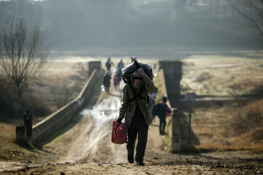 Migrants walk to enter Greece from Turkey by crossing the Maritsa river (Evros river in Greek) near the Pazarkule border gate in Edirne, Turkey, Sunday, March. 1, 2020. The United Nations migration organization said Sunday that at least 13,000 people were massed on Turkey's land border with Greece, after Turkey officially declared its western borders were open to migrants and refugees hoping to head into the European Union. (AP Photo/Emrah Gurel)