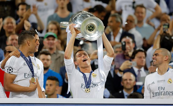 Real Madrid's Cristiano Ronaldo celebrates with the trophy after the Champions League final soccer match between Real Madrid and Atletico Madrid at the San Siro stadium in Milan, Italy, Saturday, May 28, 2016. Real Madrid won 5-4 on penalties after the match ended 1-1 after extra time.   (AP Photo/Manu Fernandez)