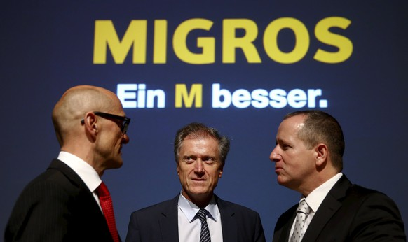 Herbert Bolliger, chief executive of Swiss retail company Migros, stands in between Chief Financial Officer Joerg Zulauf (L) and head of marketing Hansueli Siber (R) after the company's annual news conference in Zurich March 31, 2015. The slogan in the background reads,