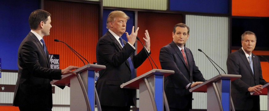 Republican U.S. presidential candidate Donald Trump shows off the size of his hands as rivals Marco Rubio (L), Ted Cruz (2nd R) and John Kasich (R) look on at the start of the U.S. Republican presidential candidates debate in Detroit, Michigan, March 3, 2016. REUTERS/Jim Young