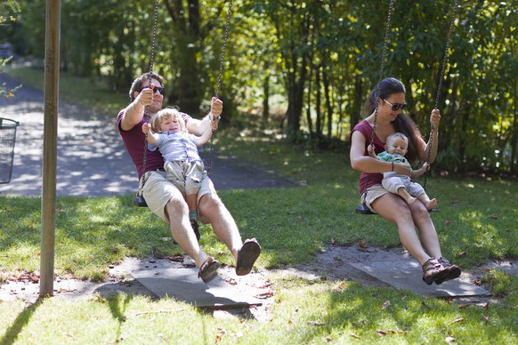 An unmarried couple and their children Marlon (2.5 years, right) and Moris (6 month, left) sit on swings, pictured on September 16, 2011, in Unterfelden in the canton of Aargau, Switzerland. (KEYSTONE/Gaetan Bally)