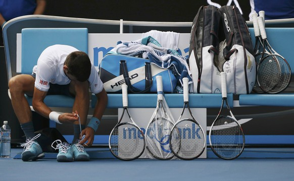 Tennis - Australian Open - Melbourne Park, Melbourne, Australia - 19/1/17 Serbia's Novak Djokovic changes his shoes while sitting next to his rackets during his Men's singles second round match against Uzbekistan's Denis Istomin. REUTERS/Issei Kato TPX IMAGES OF THE DAY