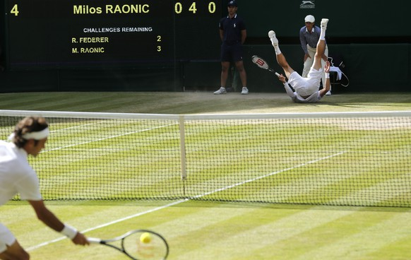 Milos Raonic of Canada falls over as Roger Federer of Switzerland plays a return during their men's singles semifinal match at the All England Lawn Tennis Championships in Wimbledon, London, Friday, July 4, 2014. (AP Photo/Ben Curtis)