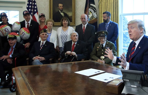 President Donald Trump is joined by World War II veterans, seated from left, Sidney Walton, Allen Jones, Paul Kriner and Floyd Wigfield, in the Oval Office of the White House in Washington, Thursday, April 11, 2019. (AP Photo/Manuel Balce Ceneta)