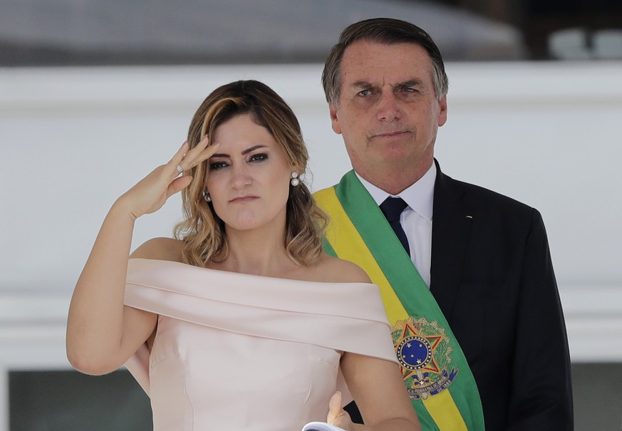With her husband, Brazil's new President Jair Bolsonaro in the background, Brazil's new first lady Michelle Bolsonaro gives a military salute from the Planalto Presidential palace, in Brasilia, Brazil, Tuesday, Jan. 1, 2019. (AP Photo/Silvia Izquierdo)