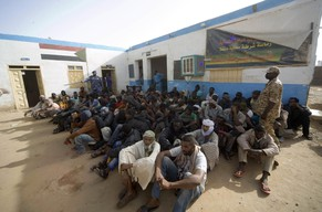 Illegal immigrants who were abandoned by traffickers in a remote desert area wait at a military base in Dongola town, after being located by Sudanese and Libyan forces, May 3, 2014. The desert area between Sudan and Libya is a major route for illegal immigrants trying to escape Sudan's war-torn regions, with many of them transiting in Libya before trying to flee to Europe across the Mediterranean Sea. REUTERS/Stringer (SUDAN - Tags: CRIME LAW CIVIL UNREST CONFLICT)