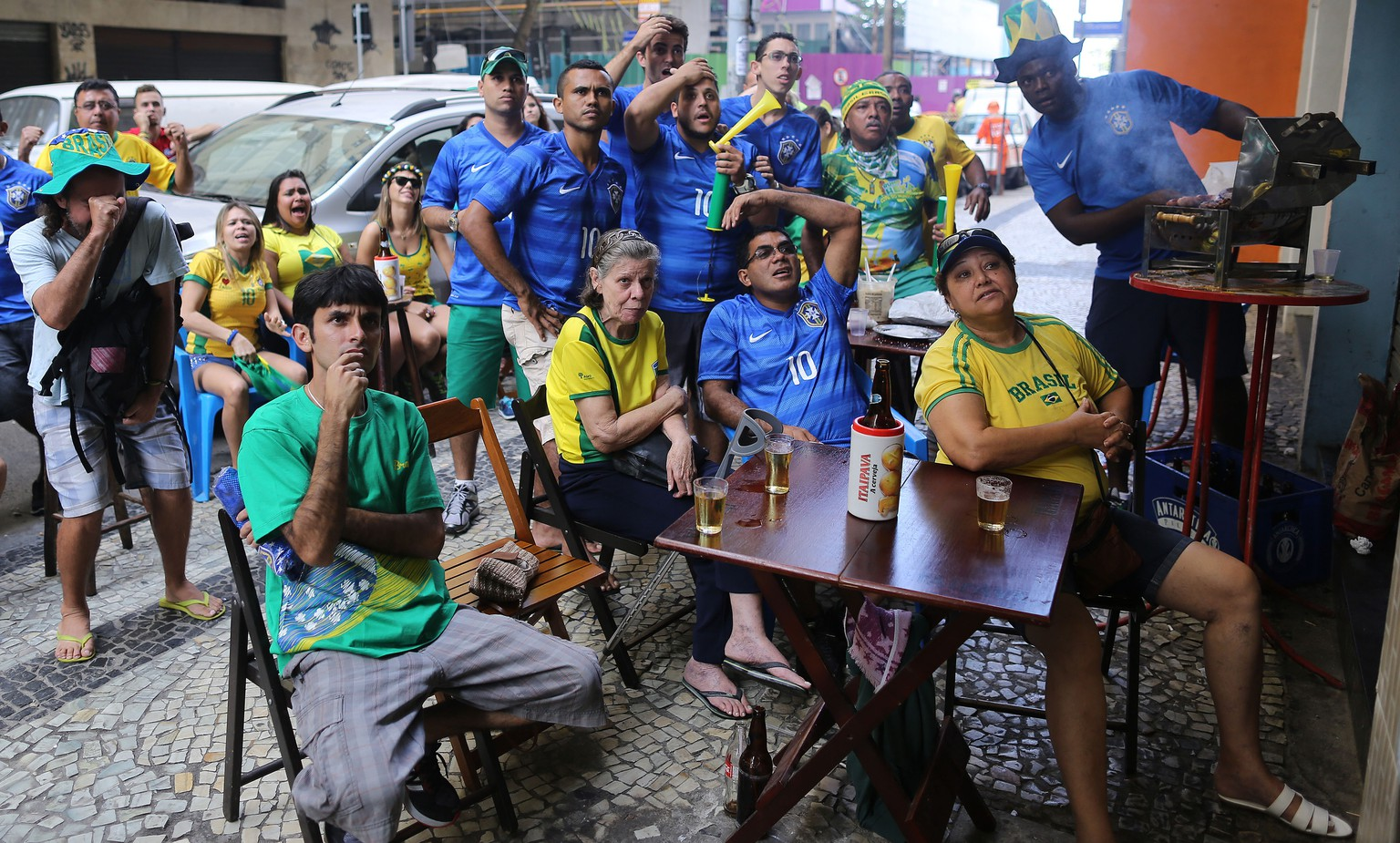 Fans of Brazil react as they watch the Brazil vs Chile soccer match on TV during the 2014 World Cup on a sidewalk at the Copacabana area, in Rio de Janeiro, Brazil, Saturday, June 28, 2014.(AP Photo/Leo Correa)