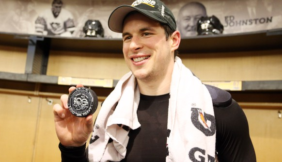 Feb 16, 2017; Pittsburgh, PA, USA;  Pittsburgh Penguins center Sidney Crosby (87) poses with the puck used for his 1000th career NHL point against the Winnipeg Jets at the PPG PAINTS Arena. Crosby assisted on a goal by left wing Chris Kunitz (not pictured) for his milestone point. The Penguins won 4-3 in overtime. Mandatory Credit: Charles LeClaire-USA TODAY Sports
