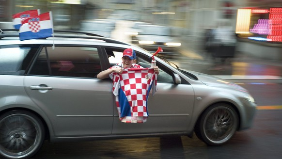 Croatian fans are holding flags out of the windows of their cars while driving on the Langstrasse in  Zurich, Switzerland on Sunday, June 8, 2008. (KEYSTONE/Gaetan Bally)