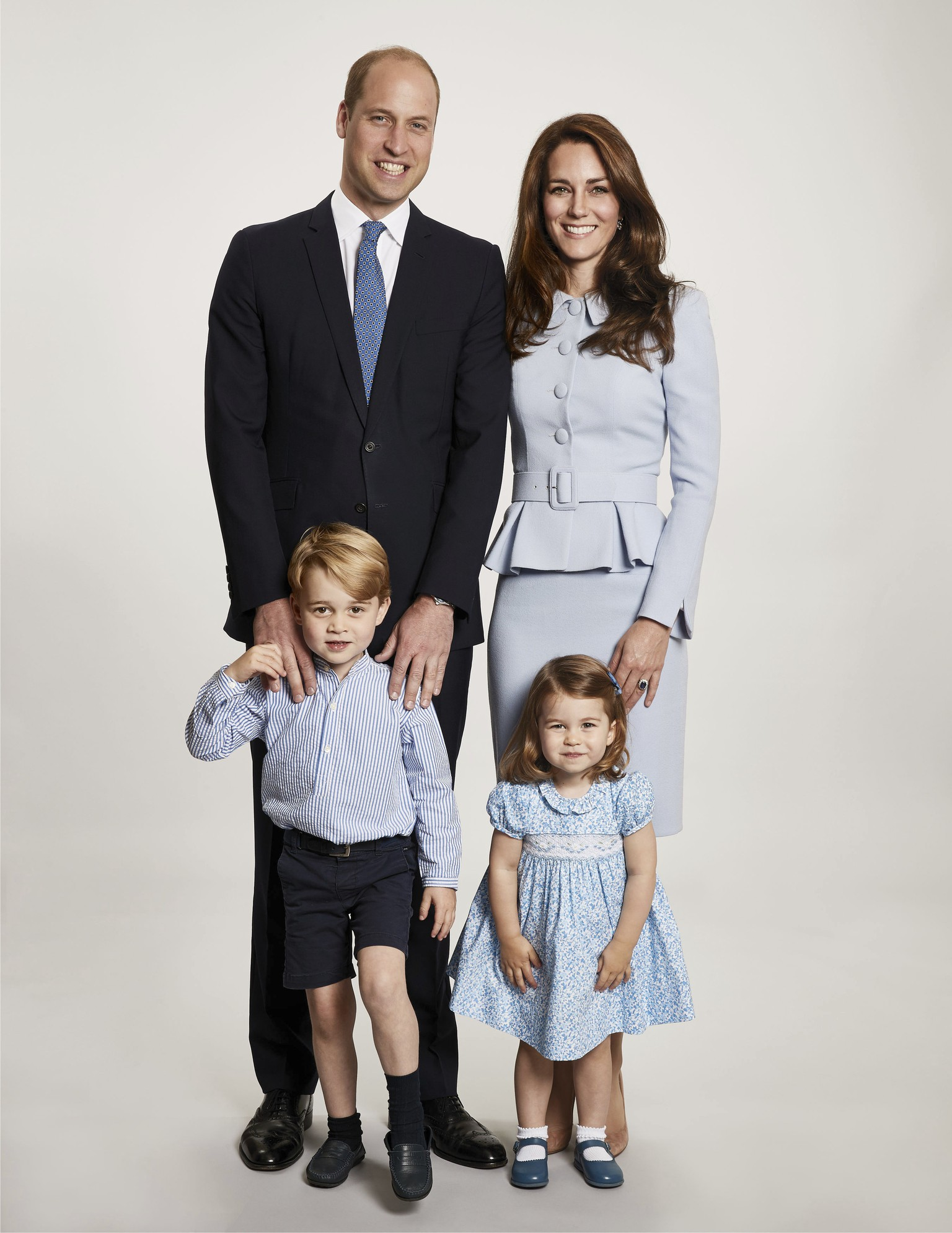 In this undated photo provided by Kensington Palace on Monday, Dec. 18, 2017, Britain's Prince William, background left and Kate, the Duchess of Cambridge pose with their children Prince George and Princess Charlotte, at Kensington Palace. The photo has been used on the Cambridges' Christmas card.  (Chris Jackson/Kensington Palace via AP)