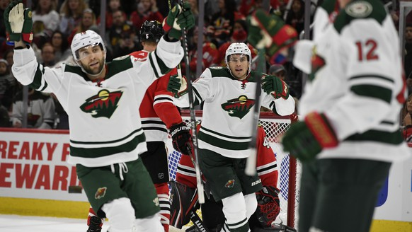 Minnesota Wild's Zach Parise center, and Jason Zucker left, celebrate after teammate Eric Staal,(12) scored a goal during the first period of an NHL hockey game against the Chicago Blackhawks,Sunday, Dec. 15, 2019, in Chicago. (AP Photo/Paul Beaty)