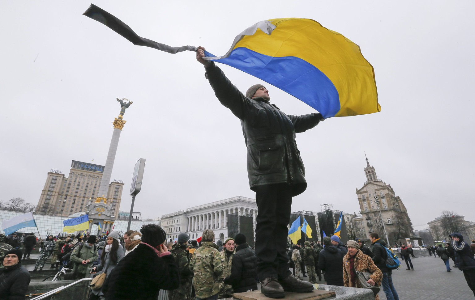 epa04628704 An Ukrainian man waves a National flag at the Independence square in Kiev, Ukraine 20 February 2015. Ukrainians marked the first year anniversary of the escalated violence in Maidan where it resulted in at least 100 people being killed. The leaders of France, Germany, Russia and Ukraine agreed in a phone call, to 'rigorously implement' the peace agreement signed last week in Minsk. The leaders also condemned the recent ceasefire violations and discussed the consequences of 'events in Debaltseve' for the peace agreement.  EPA/SERGEY DOLZHENKO